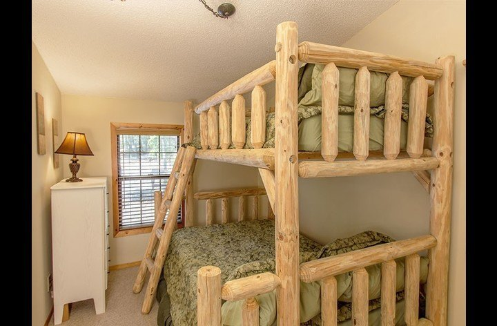3rd bedroom with custom log bunk bed that has a full over twin & flat screen TV.
