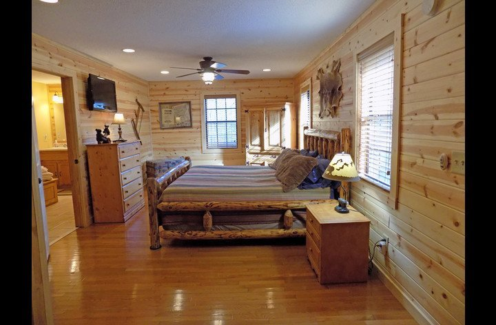 Master bedroom with king size log bed and HDTV